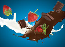 Caídas del chocolate y de la fresa en la leche Fotos de archivo libres de regalías