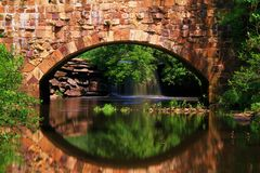 Caídas en la reflexión en el puente de piedra ocultado fotos de archivo libres de regalías