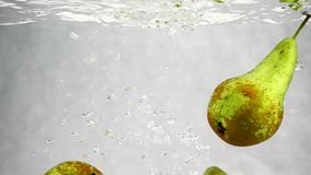 Caídas verdes de las peras en el agua con muchas pequeñas burbujas Vídeo de frutas en fondo blanco aislado metrajes
