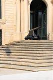 Cañón antiguo que guarda la entrada al palacio en la capital de Malta, La Valeta foto de archivo