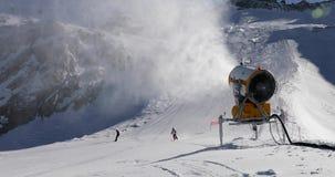 Cañón de la nieve que trabaja en la cuesta en las montañas de Italia metrajes