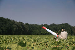 Cañón del propano en un campo con las cosechas jovenes fotografía de archivo libre de regalías