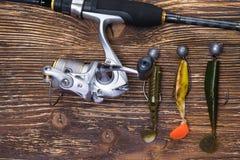 Caña de pescar con el carrete y trastos para pescar en el fondo de tableros oscuros foto de archivo