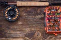 Caña de pescar con un carrete y un sistema de cebo, de mosquitos, de mariposas y de polillas, en un viejo tablero oscuro, fondo,  foto de archivo
