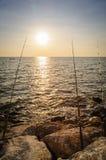 Caña de pescar de la silueta en una playa Imagenes de archivo