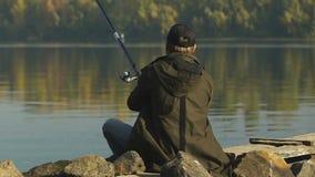 Caña de pescar del bastidor del pescador, sentándose en la orilla del río, afición recreativa almacen de metraje de vídeo