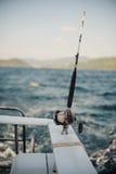 Caña de pescar del carrete en tenedor del cromo en el barco Foto de archivo