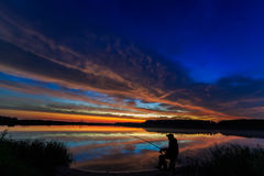 Caña de pescar del pescador en el amanecer en el lago Imagen de archivo libre de regalías