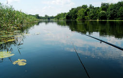 Caña de pescar en el fondo de la superficie lisa del agua al mediodía Imagen de archivo
