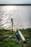 Caña de pescar en la hierba cerca del lago Foto de archivo