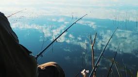 Caña de pescar en las manos de un pescador Orilla del lago Agua tranquila y tranquila lisa con la reflexión de nubes Hermoso almacen de metraje de vídeo
