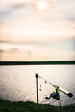 Caña de pescar en puesta del sol hermosa en el borde del lago Foto de archivo