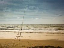 Caña de pescar que se coloca en la playa de la tarde Imágenes de archivo libres de regalías