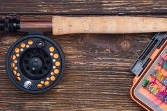 Caña de pescar y carrete con una línea anaranjada cerca del cebo para pescar en un fondo de madera imagenes de archivo