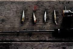 Caña de pescar y cebo de pesca en la tabla de madera fotos de archivo libres de regalías