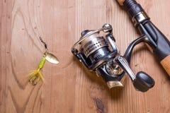 Caña de pescar y señuelo en la superficie de madera Imagen de archivo libre de regalías