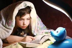 Caña del muchacho el libro antes del sueño con el pequeño gatito foto de archivo