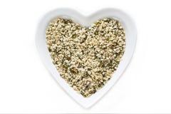 Cañamones en cuenco de cerámica en forma de corazón Fotografía de archivo libre de regalías
