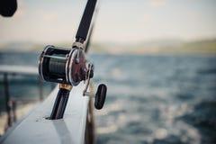 Cañas de pescar del barco sobre un paisaje marino nublado hermoso Fotografía de archivo