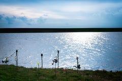 Cañas de pescar en el borde de un lago Imagen de archivo libre de regalías