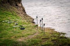 Cañas de pescar en el borde de un lago en la hierba Imagenes de archivo