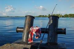 Cañas de pescar en el muelle Foto de archivo