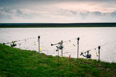 Cañas de pescar en la hierba en el borde del río Imagenes de archivo