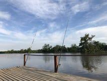 Cañas de pescar en la orilla del río imagenes de archivo