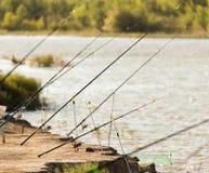 Cañas de pescar en la orilla del río en naturaleza Imagenes de archivo