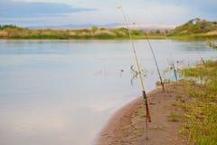 Cañas de pescar en los bancos del río Foto de archivo libre de regalías