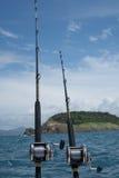 Cañas de pescar en un barco sobre el mar azul, el cielo y la isla verde Fotografía de archivo