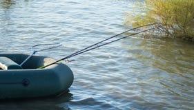 Cañas de pescar para pescar en un barco en el lago Fotos de archivo