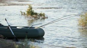 Cañas de pescar para pescar en un barco en el lago Foto de archivo