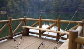 Cañas de pescar que se inclinan contra el carril de mano en un infante de marina de madera imágenes de archivo libres de regalías