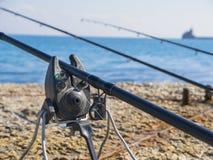 Cañas de pescar y marcador del insecto en la costa Foto de archivo libre de regalías