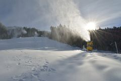 Cañones de la nieve que hacen nieve artificial en una cuesta del esquí en Poiana Brasov Imágenes de archivo libres de regalías