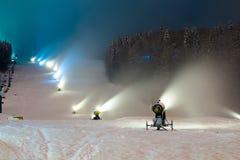 Cañones de la nieve que trabajan en la noche en las montañas Imagen de archivo libre de regalías