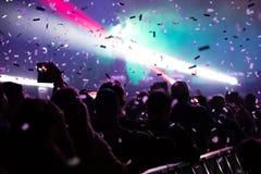 Cañones del confeti que lanzan confeti sobre la muchedumbre que va de fiesta Foto de archivo libre de regalías
