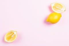 Cała i pokrojona cytryna na różowym tle Fotografia Stock