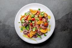 Cała ośmiornicy sałatka z pomarańcze, pomidorami i cress sałatką na bielu talerzu, Odgórny widok zdjęcie stock