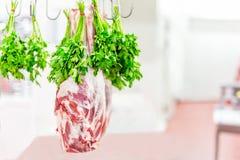 Cała surowa jagnięca noga wieszająca na haczyku z wiązką pietruszka przy rynkiem lub sklepem Mięso przygotowywający dla kucharza Fotografia Royalty Free