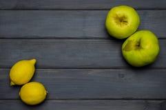 Całe cytryny nad i zielony dojrzały jabłko jesieni żniwo od zmroku - szary drewniany stół Obraz Stock