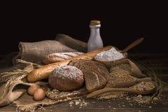 Całej banatki chleb, mleko, mąka i sukienna torba na drewno stole, obrazy stock