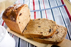 Całej banatki chleb ono ślizgał się w drewnianym talerzu na stole z tablecloth Zdjęcia Stock