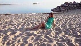całkowity plan Seksowna kobieta sunbathing i bawić się z włosy na plaży zbiory