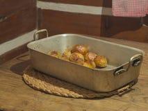 Całość piec grule w nieociosanej wypiekowej niecce na drewnianym stole w Tim fotografia royalty free