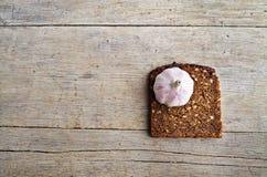 Całość zbożowego brown chleba i gryzący czosnek Zdjęcia Royalty Free