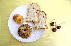 Całość zbożowego chleba, rodzynka chleb na wierzchołka talerzu i wiśnie, fotografia royalty free