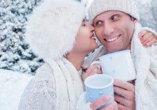Całować pary z gorącymi herbacianymi filiżankami na śnieżnej lasowej haliźnie Obraz Royalty Free