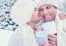 Całować pary z gorącymi herbacianymi filiżankami podczas śnieżnego lasowego spaceru Obraz Stock
